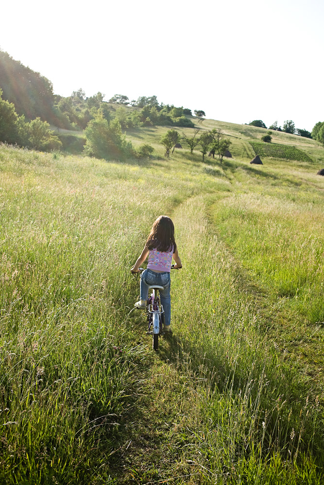 Zece-Hotare village, Romania.Andrada, 6 years old, riding her bicycle at the end of a June day in the field at the rear of Ana Matei's farm house.