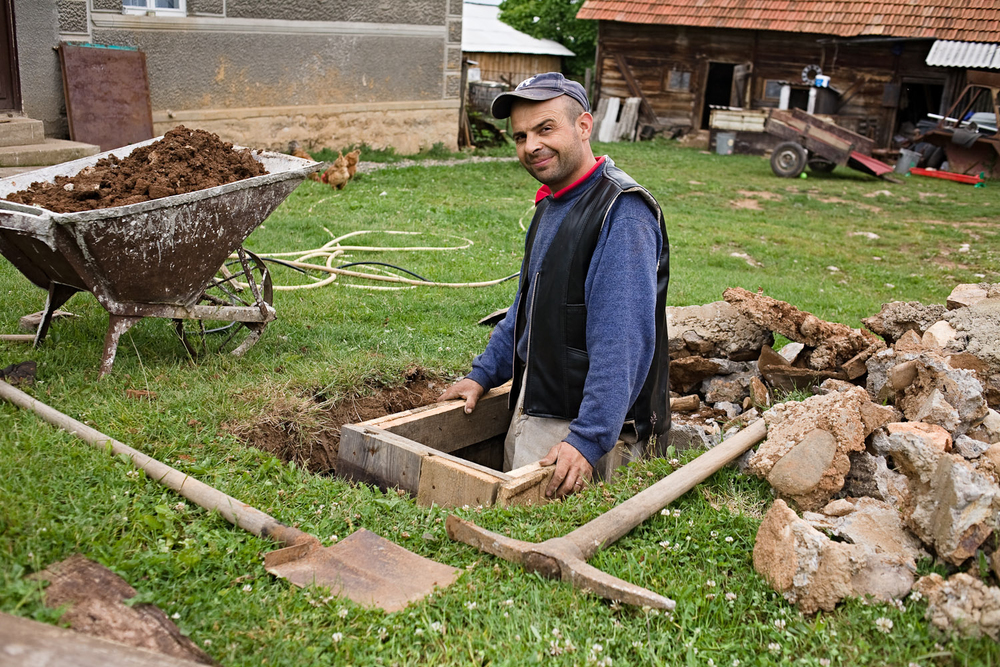 Zece-Hotare village, Romania. Florin making the most of the warm weather to create a cold-proof enclosure for his water pipes in the garden. With a continental climate and six month winters where temperatures can fall below -30ˇC, such preparatory work in the fine season is essential.