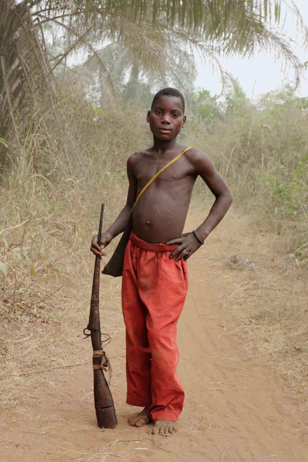 Boy hunter with a locally made rifle on the road to Awai.
