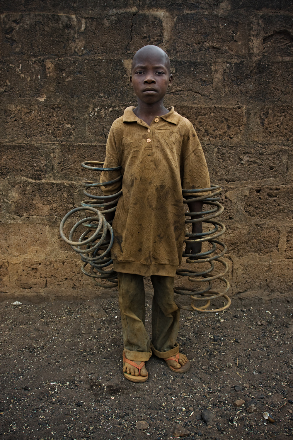 Working child carrying springs, Ketou.