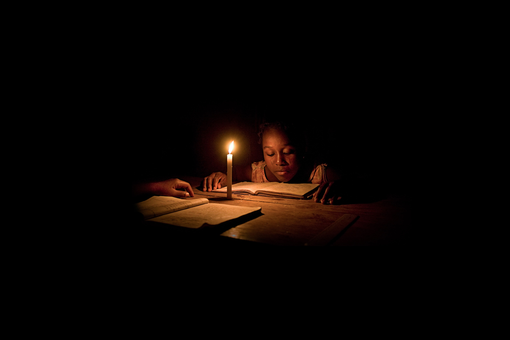 Nafi doing her homework by candle light at night, Ketou.
