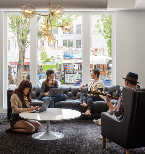 Floor-to-ceiling windows open this collaborative living room-style space to the SW 3rd and Washington food carts.