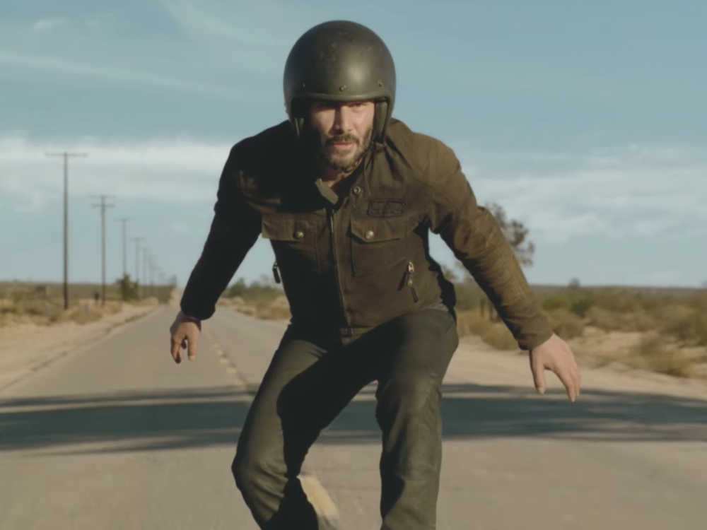 Keanu Reeves surfs a motorcycle in the Super Bowl Squarespace commercial.