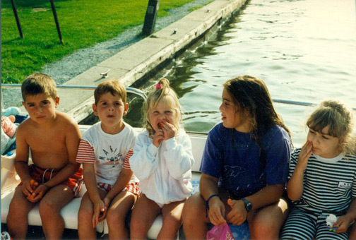 Chilling on the dock.  I'm rocking a jailbird chic look. Note my messy hair + face (this lasts through 1999).  I'm sitting with family friends.  We were at their cottage in Lagoon City, on Lake Simcoe.