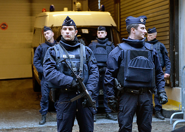 Police stand guard outside the offices of French daily newspaper Libération in Paris as the remaining members of the Charlie Hebdo editorial staff arrive for a meeting on Jan. 9, 2015.