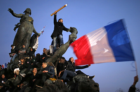 A man holds a giant pencil as he takes part in a solidarity march along with hundreds of thousands of French citizens in the streets of Paris on Jan. 11, 2015. -- Photo by Stephane Mahe/Reuters
