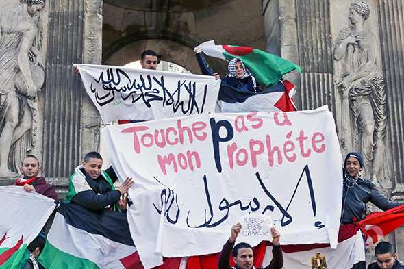 """French Muslim youths hold a banner reading """"Do not touch my prophet, anything but the Messenger of Allah"""" as they gather in central Paris on Jan. 18, 2015. -- Photo by Pascal Rossignol/Reuters"""