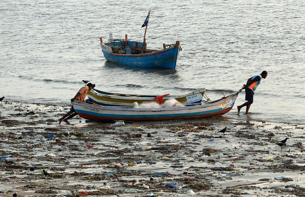 Indian fishermen pushed their boat through plastic waste last month in Mumbai.   Credit Punit Paranjpe/Agence France-Presse — Getty Images