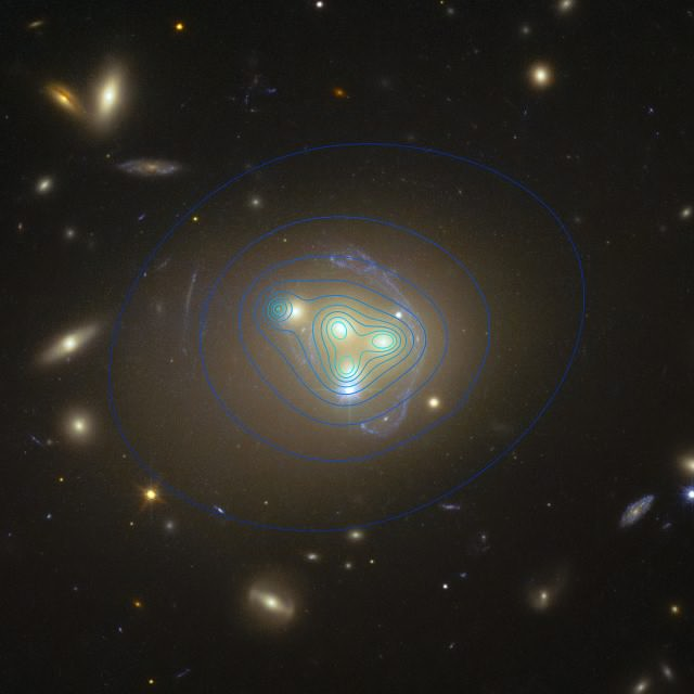 Abell 3827, imaged by the Hubble Space Telescope. The four main objects at the center are the galaxies discussed in the article. The strange pale blue objects surrounding them are lensed images of a much more distant background galaxy. The blue contour lines show the distribution of dark matter. The top-left galaxy of the four has dark matter clearly offset from the visible galaxy, perhaps implying lag due to friction, caused by self-interactions.