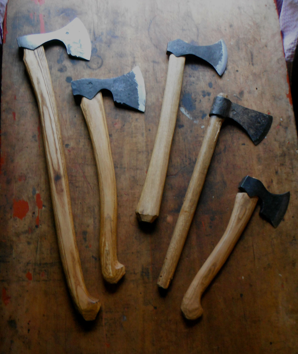 "All in the family: (l to r) bearded axes with 27"" & 19"" handles, early viking belt axe, tomahawk, Scandinavian carving hatchet."