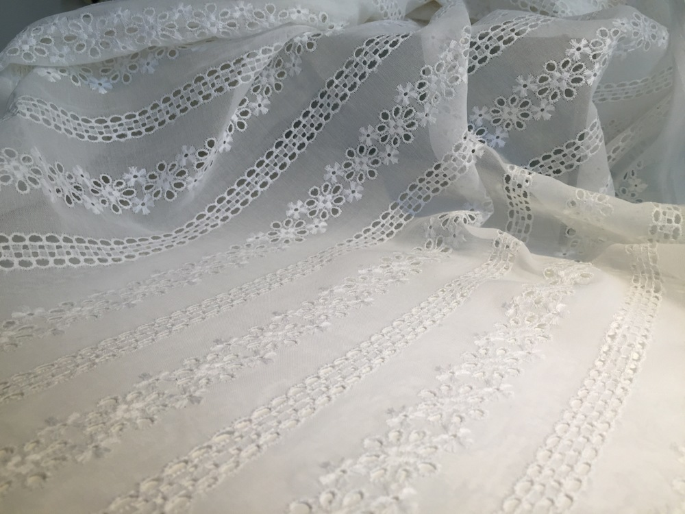 Broderie Anglaise: a light but solid fabric (like a cotton voile) which is embroidered with a pattern composed of small round or oval holes which are bound in overcast (buttonhole) stitches. These little holes, commonly known as eyelets, can be accompanied by embroidered details, like the small flowers seen above. This style originated in the 16th century in Eastern Europe, but was popularized in the Victorian era in England.