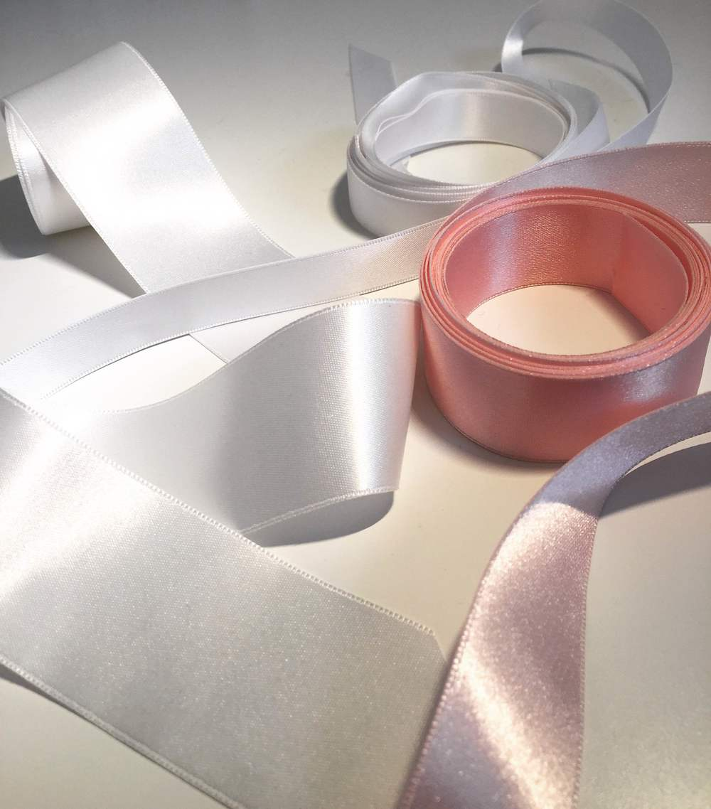 "Satin Ribbon is probably the most commonly thought of trim when it comes to bridal belts and sashes. Available in a ton of colors and variety of standard widths, usually between 1/8th"" to 3 or 4"", these can also come in a variety of qualities. There are thin, paper-y, stiff varieties that work better on a hat or an Easter basket, but a good bridal satin trim to search for or ask for is a double-faced polyester satin trim. Pictured here are a few of these, which are shiny on both sides, and slightly thicker than a basic satin trim. Thickness is especially important if you have a lace dress with a texture that might show through as bumps under a thinner satin. Also consider the width of the ribbon compared to the waistline on your dress and your bust size. A very thin trim may be the best way to bring waist definition on delicate dress or for a bride with a larger bust, while a more substantial dress or a bride with a smaller bust may benefit from a 2"" wide trim. Much bigger than 2"" is often tricky, because the shape of a waist usually curves in and out at about 1"" above and below. Keeping an extra wide trim in place may require seams or darts to contour properly."