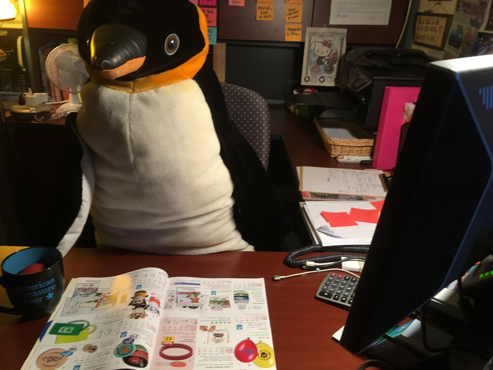 Our Penguin is hard at work browsing a catalog.