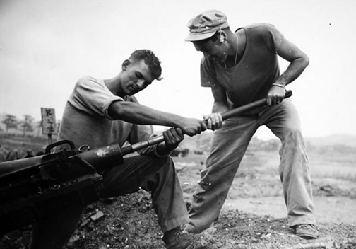 Artillerymen of the 11th Marines swabbing the barrel of their pack howitzer during the Okinawa campaign.