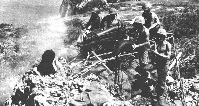 "This 75mm pack howitzer, nicknamed ""Miss Connie,"" is firing into a Japanese-held cave from the brink of a sheer cliff in southern Tinian."