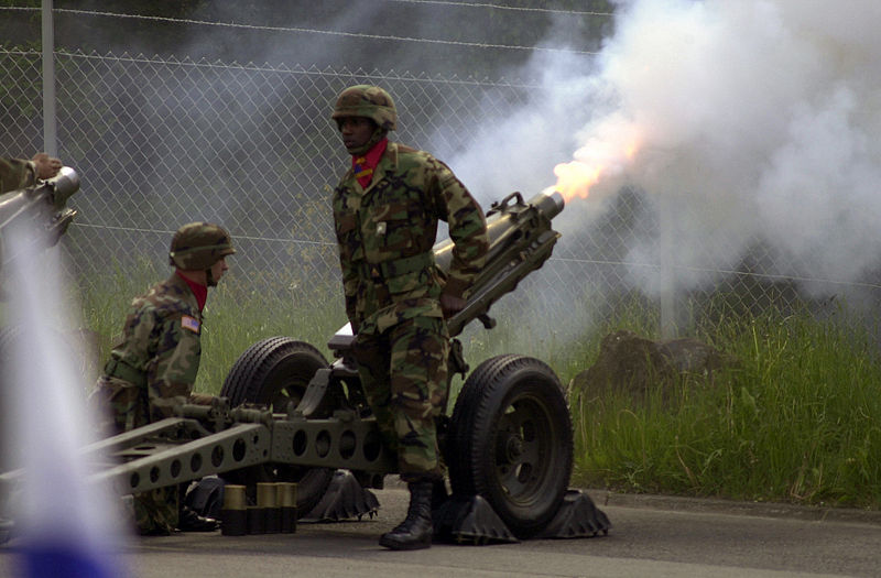 Members of Charlie Battery, 1st of the 94th Field Artillery, US Army, Europe, fire a 75 mm Pack Howitzer M116
