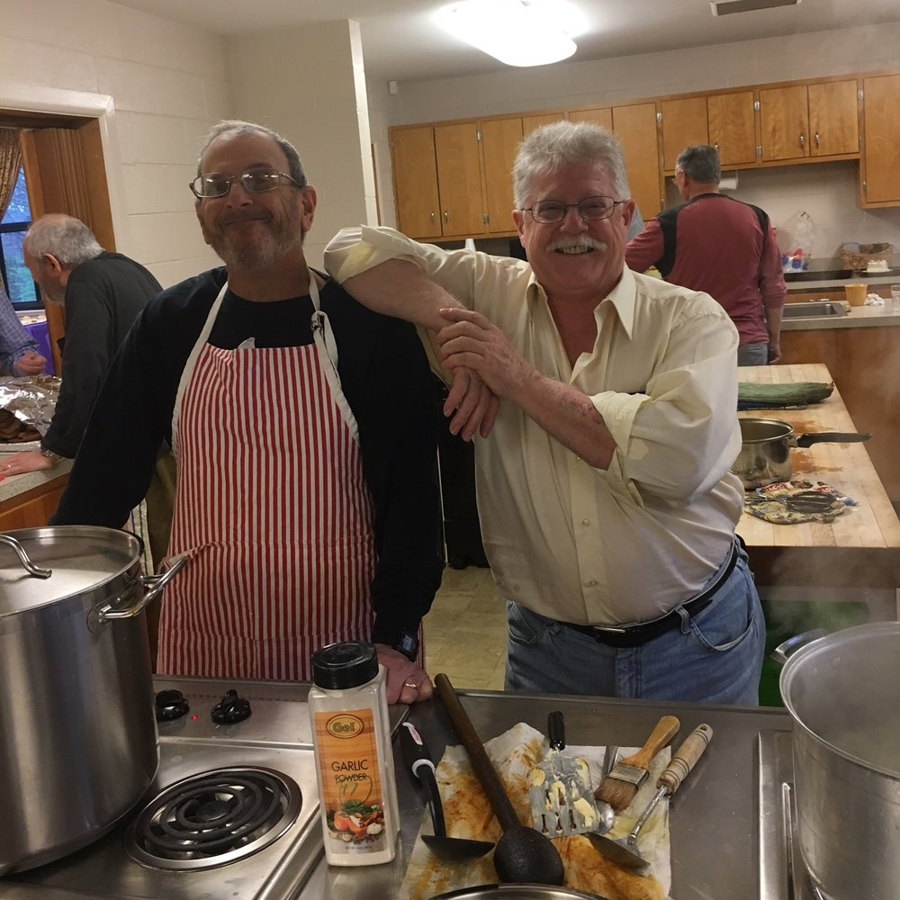 Men's club leaders hard at work preparing dinner for the Lions club .