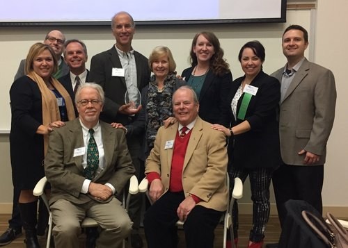 Past presidents gather around Thane Maynard. Back row, from left: Carrie Phillippi, APR; Rob Pasquinucci, APR, Mike Boehmer, APR; Thane Maynard, Lee Oberlag, APR; Shara Clark, APR; Lauren Doyle, APR; Jonathan Kissell, APR. Front row, Rick Pender, APR, Fellow PRSA; and Tom Schick, APR, Fellow PRSA.