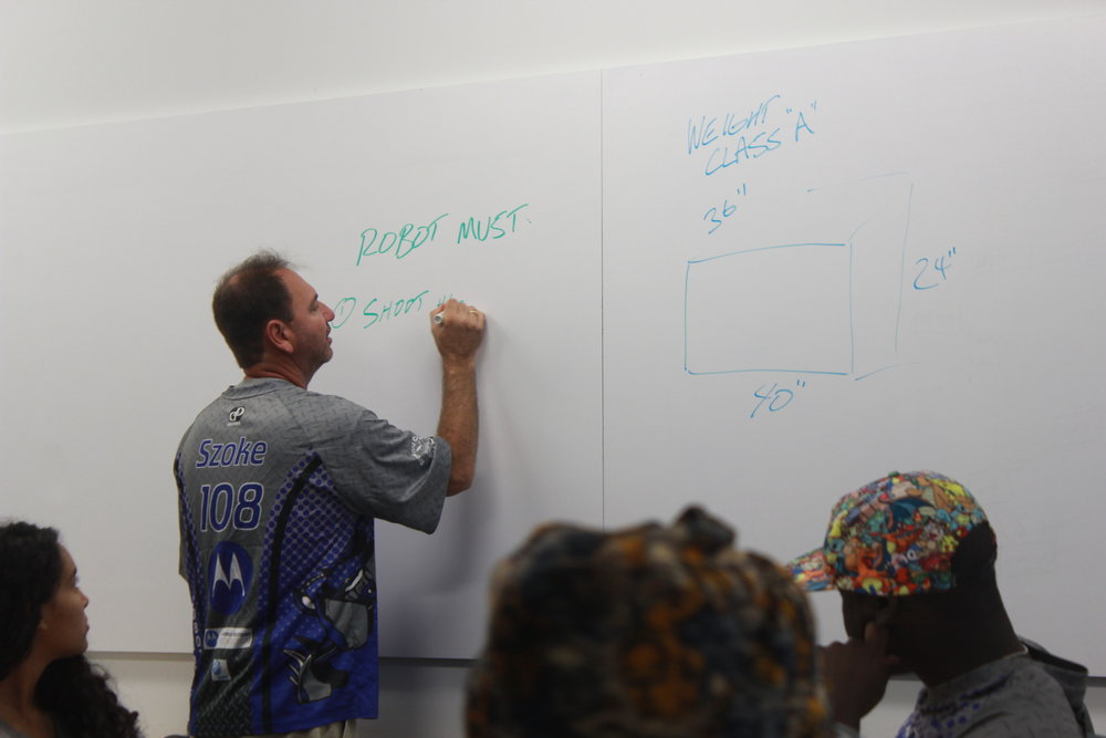 Team mentor, Mr.Szoke, writes on the white board as the entire SigmaC@T team discusses the FRC Steamworks game and possible strategies for hypothetical robots.