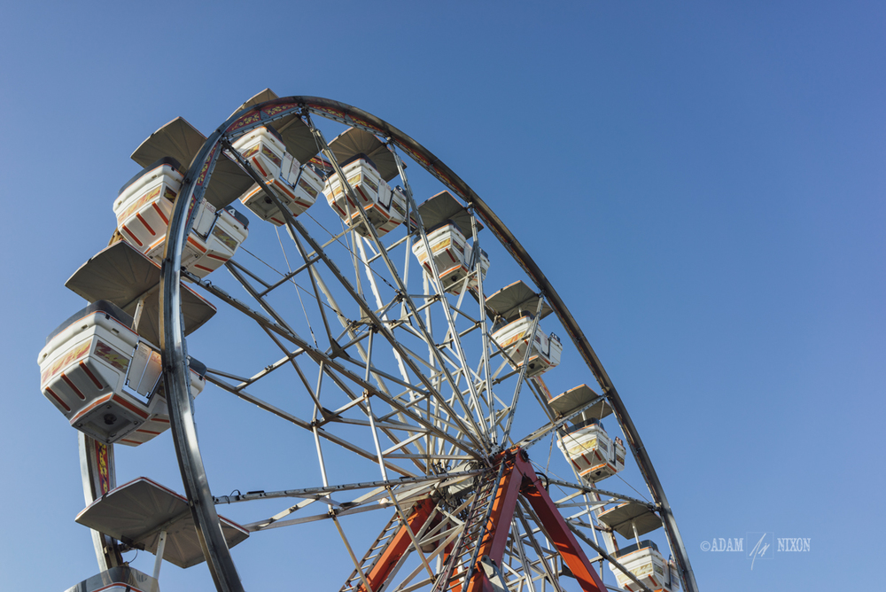Ferris wheel against a blue sly at a carnival
