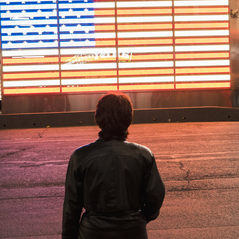 A woman in a black leather jacket looking at an american flag ma