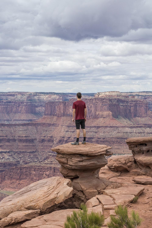 Teenage boy standing a rock pillar looking out over a vast lands