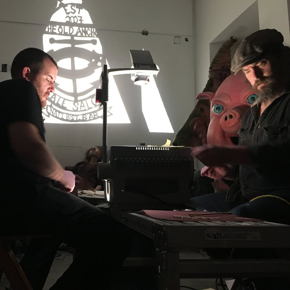 Stuart Window and David Higgins manning the overhead projector during a performance of  A Haunting in Buzzard's Bay  at Big Nazo Studio in Providence with Jeremy Fortier playing viola and Vanessa Gilbert singing just out of the frame.