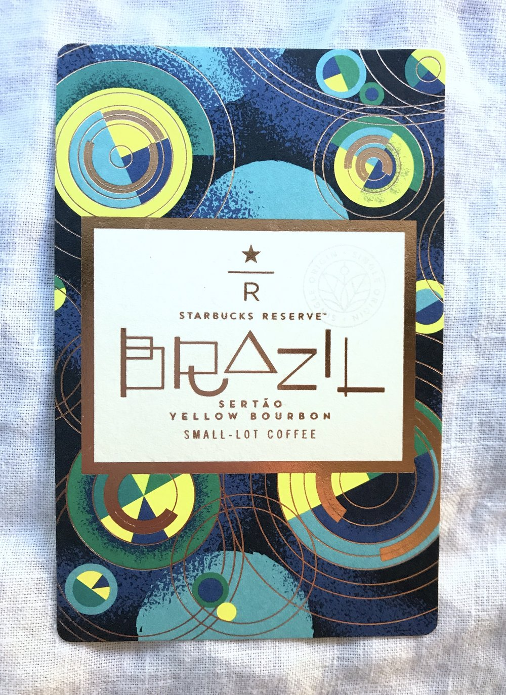 Starbucks Reserve - Brazil Sertao Yellow Bourbon - The inspiration behind Brazil Sertao Yellow Bourbon comes from the region and its rich agriculture. The Carmo de Minas region is known for its coffee production but especially its Yellow Bourbon variety. The design of the circles represent the birds-eye-view of this diverse agricultural landscape. Plots of land are often farmed in a circular irrigation pattern. The circles are also a representation of family. The Serato Estate, in which this variety comes from, is a large family firm with more than 100 years history in the production and commercialization of high-quality coffee.