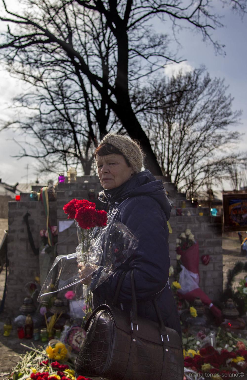 Tatiana deja un ramo de flores en uno de los altares homenaje a las víctimas del Maidan de Kiev, (Ucrania). Foto: María Torres-Solanot ©