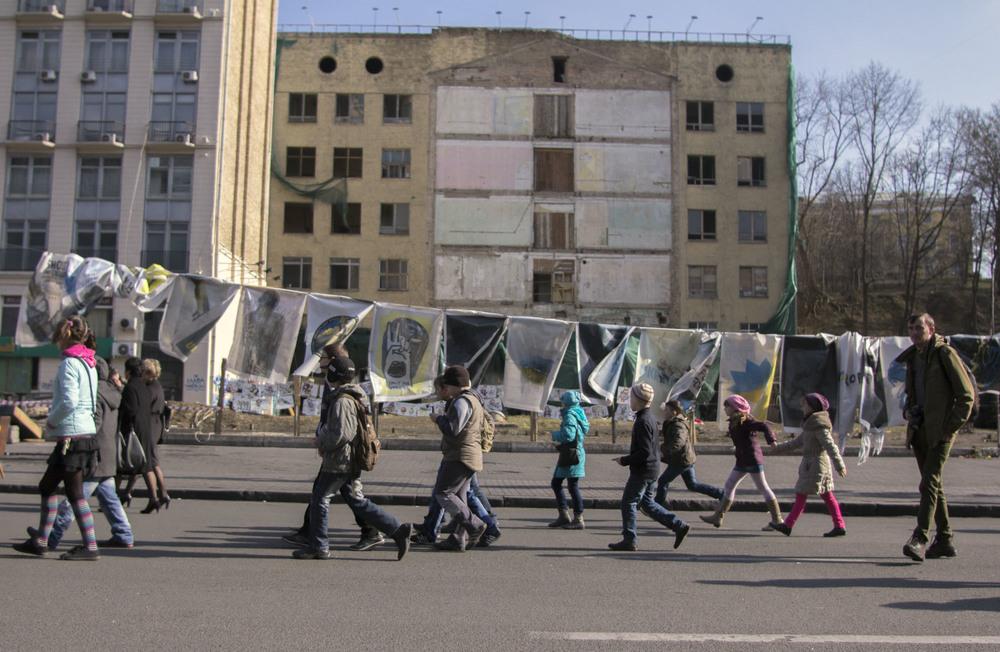 Niños caminando por delante del arte de calle del Maidan en Kiev. Foto: María Torres-Solanot ©
