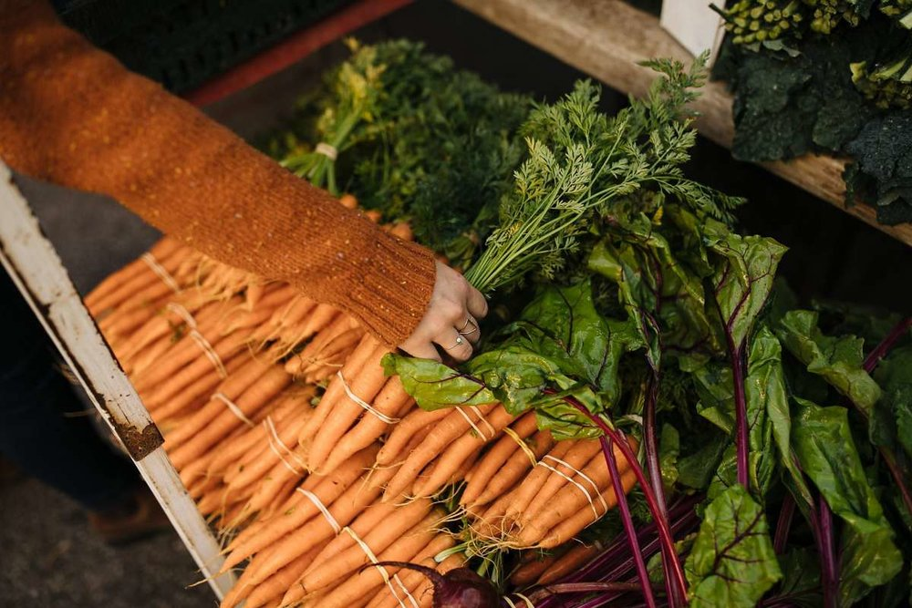 Photo credit: Mason Trinca for the  San Francisco Chronicle .  Kendra Aronson  grabs a bunch of carrots at one of her favorite booths, Domingo Farms in Arroyo Grande, at the Farmers Market in San Luis Obispo.