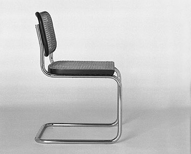 BR04: 1928  |                                      Marcel Breuer                                        Side chair in chrome-plated tubular steel. Natural or black lacquered beechwood frame with woven cane insets.