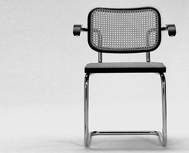 BR05: 1928  |                                      Marcel Breuer                                        Arm chair with frame in chrome plated tubular steel. Seat and back of natural or black lacquered beechwood with machine-caned insets. Flat welded endcaps.