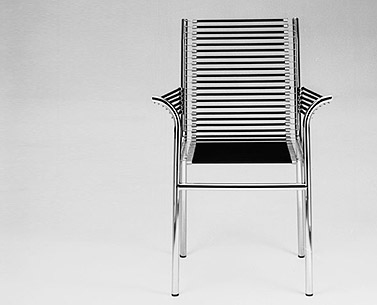 HE25: 1928-30  |                                      René Herbst                                        Armchair with chrome-plated tubular steel frame. Seat, back and arms in black elastic cords. Also available with lacquered frame.
