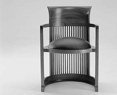 "WR04:   1937  |                                      Frank LLoyd Wright                                        Barrel chair in solid cherrywood with back fillets. Available walnut or black painted. Seat upholstered in expanded foam covered with fabric or leather.   This chair was designed for the ""Wingspread"" house, planned for Herbert Johnson in 1937. It is considered a more evolved version of a project for a barrel-shaped chair originally designed by Wright for Darwin D. Martin's house in 1904."