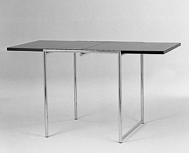 GR69:  1925/28  |                                      Eileen Gray                                      Folding table with base in chrome plated tubular steel. Laminate top.  In 1922 Eileen Gray opened a showroom in Rue du Faubourg St. Honoré  where she put the  furnishings and accessories (carpets, tubular metal furniture and lacquered furniture) she had designed for Jean Désert's firm up for sale. This table was part of the collection.