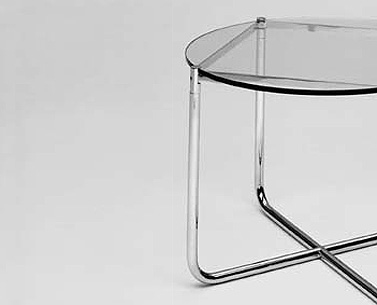 MI19:  1930  |                                      Ludwig Mies Van Der Rohe                                      Table with base in chrome plated flat bar and tubular steel. Glass top.   The round coffee table was exhibited for the first time at the Weißenhof in 1927. It was afterwards employed by Mies as part of the furnishings for Tugendhat house in Brno in 1930. It was initially produced by Berliner Metallgewerbe Joseph Müller, and from 1931 by Bamberg Metalwerkstätten.