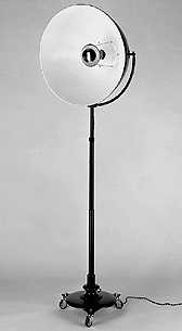 FO68:  1923  |                                      Mariano Fortuny                 Floor lamp with base in black lacquered cast iron, assembled on wheels; adjustable steel rod, black lacquered; adjustable reflector in black lacquered aluminium; shade in chrome-plated aluminium. Max recommended 500w.