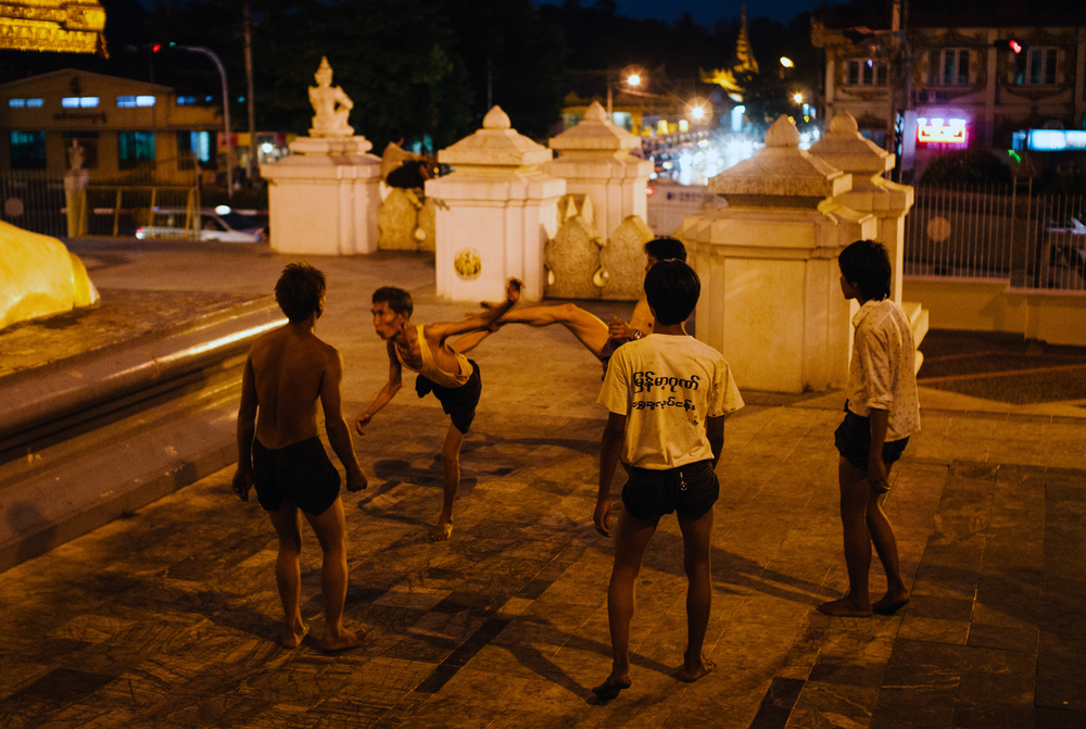 A late-night game of Rattan ball, lit by the 99-meter Shwedagon Pagoda.