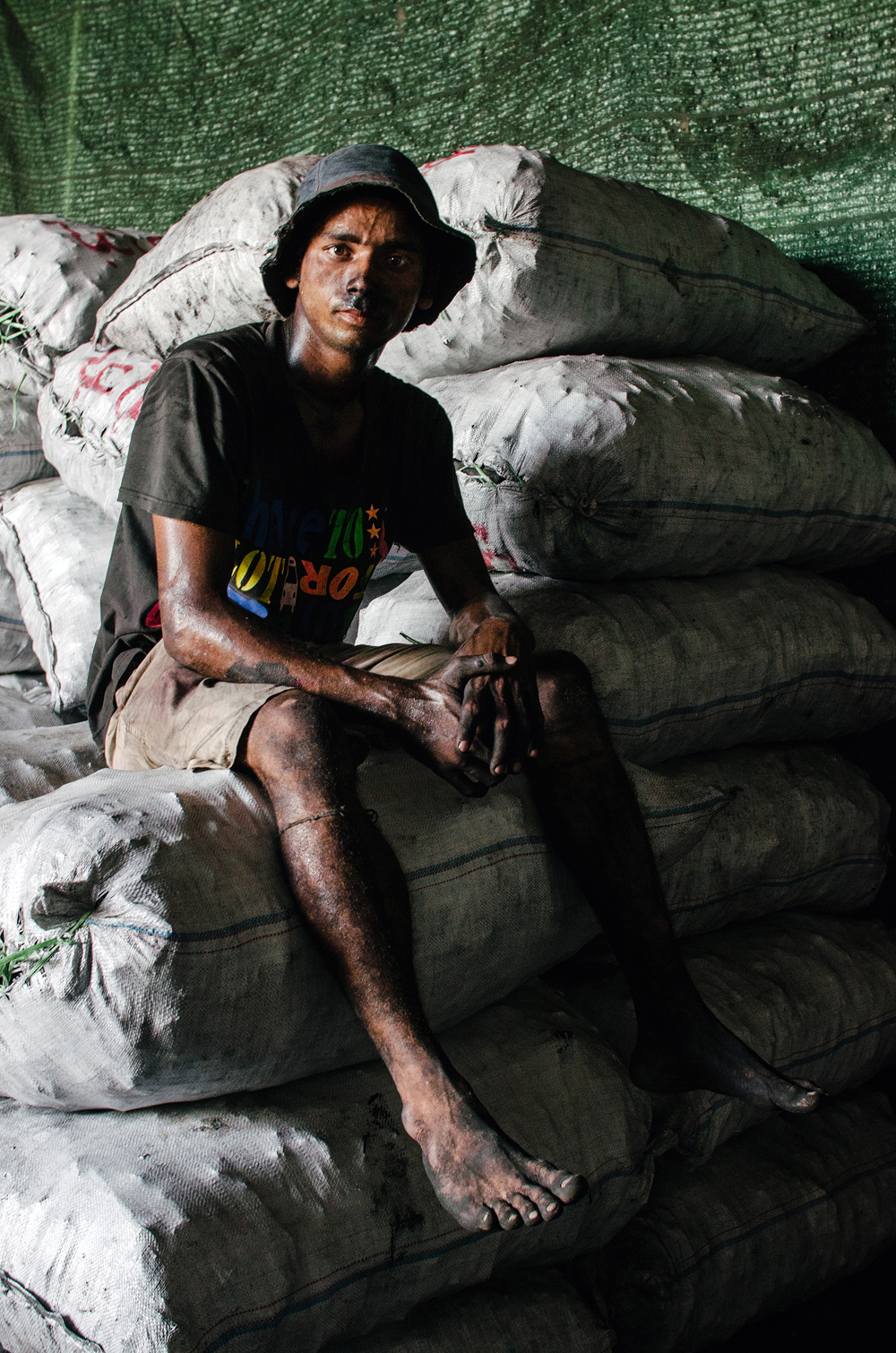 A worker at a local coal-packaging warehouse pauses for a portrait.