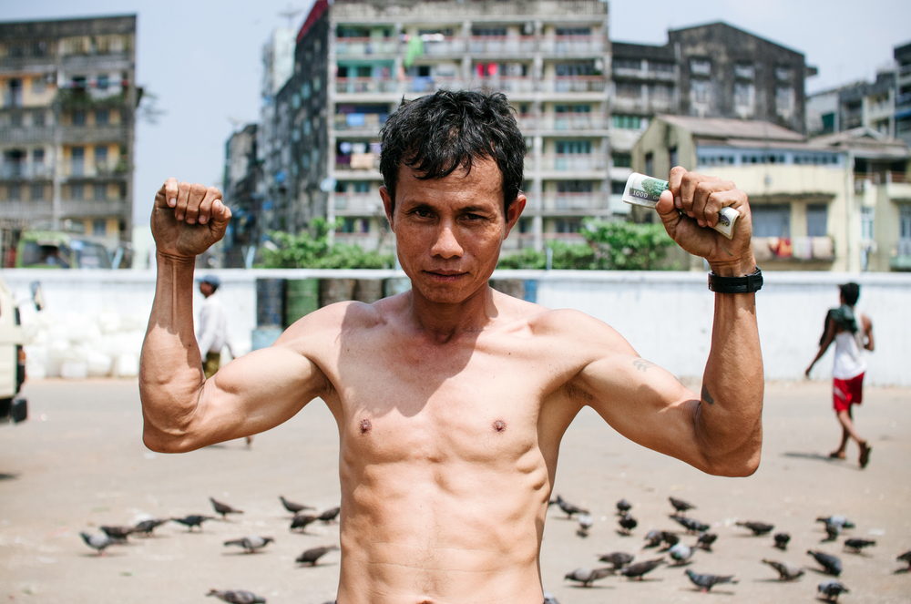 A local boxer poses between loading cargo onto a ship bound for Mandalay.