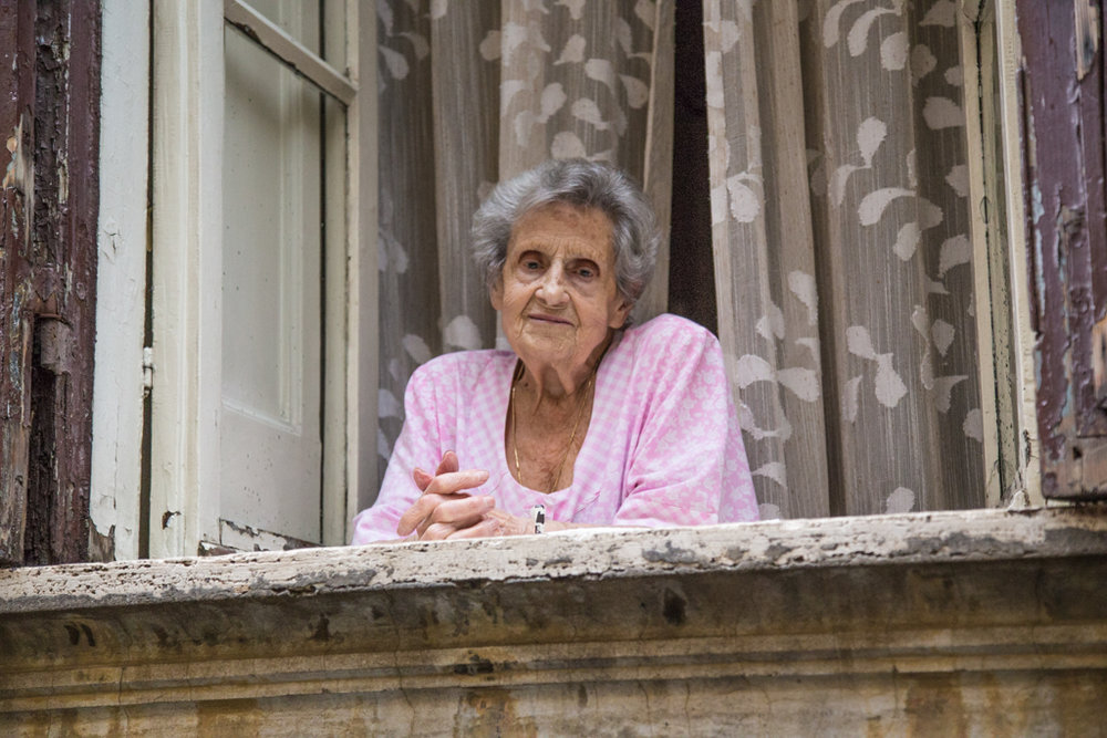 An elderly woman at her window in Rome
