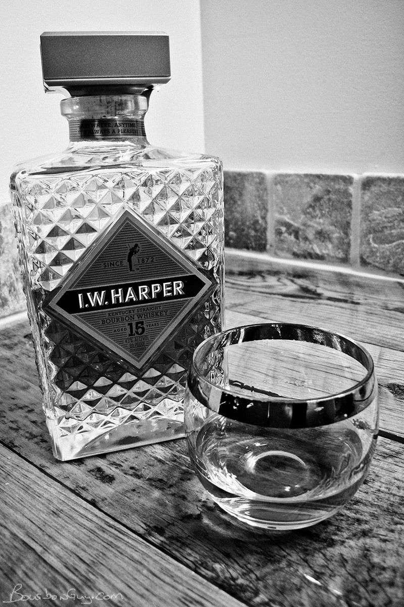 IW Harper 15 year old bourbon in decanter shaped bottle. A glass of bourbon on the side.