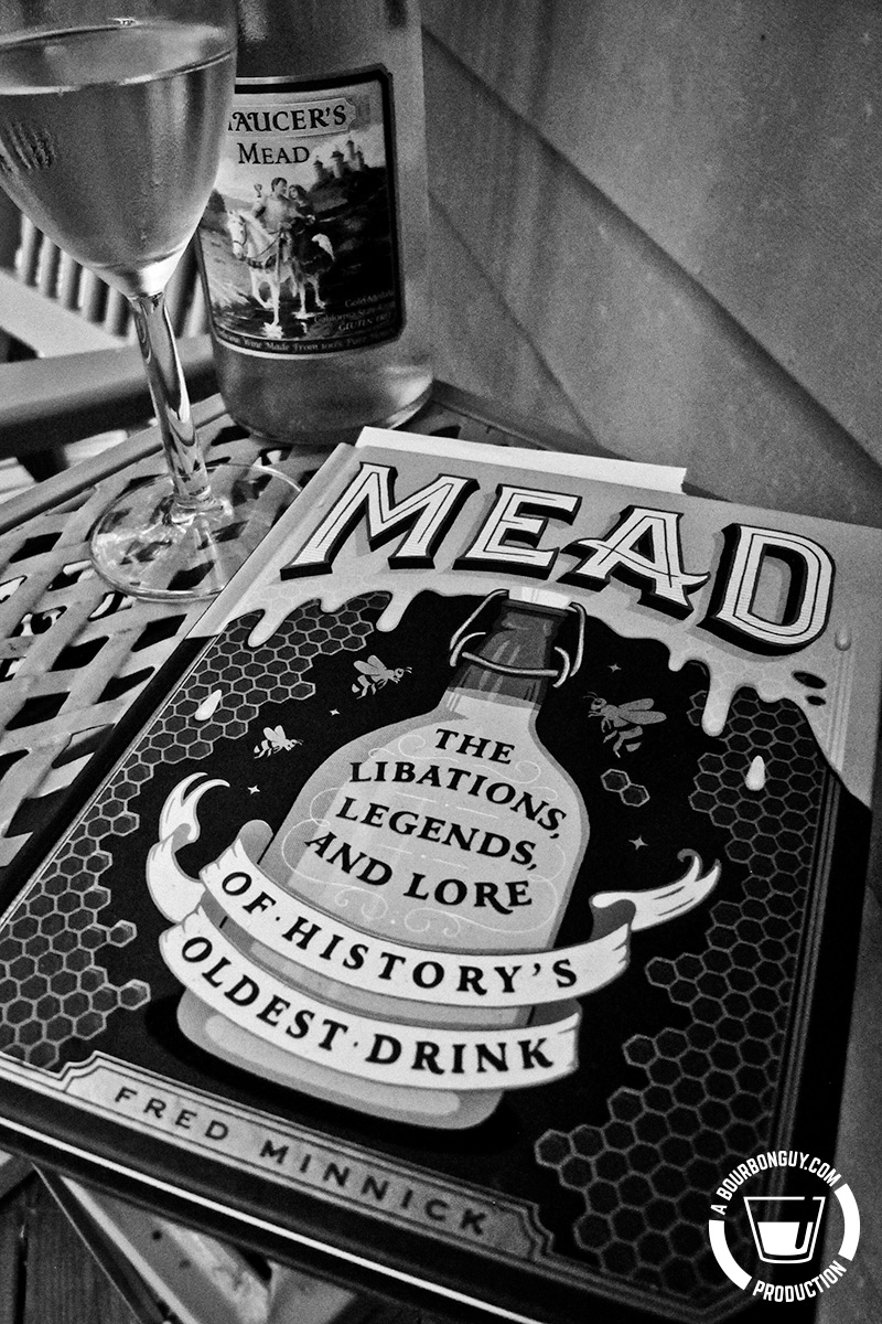 IMAGE: The book Mead: The Libations, Legends, and Lore of History's Oldest Drink by Fred Minnick laying on a table by a glass of mead and a partially filled bottle of mead.