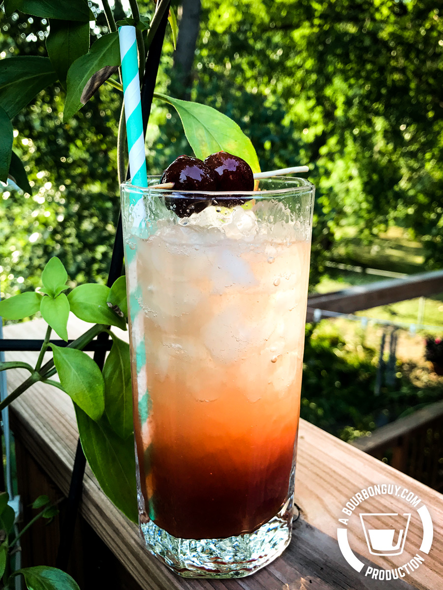 IMAGE: An antique collins glass filled with liquid ranging from clear at the top to a cloudy red at the bottom. Two cherries on a skewer are balanced on the rim as a garnish.
