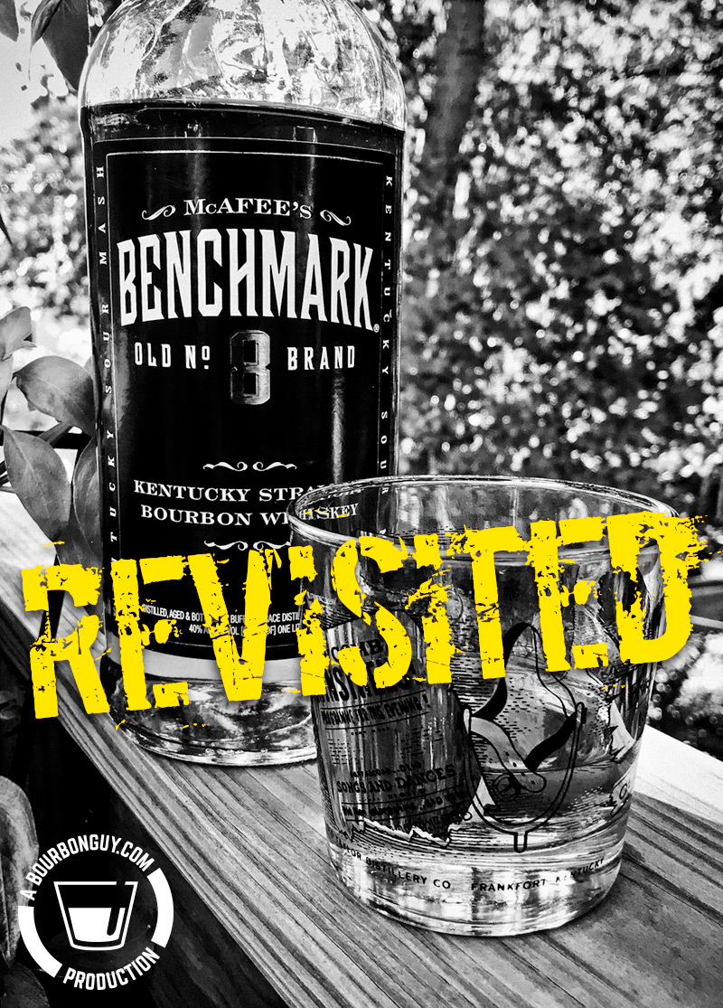 IMAGE: A bottle of Benchmark Bourbon, from the front with a glass beside it. Flanked by leaves.