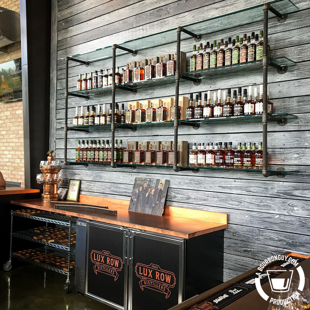 IMAGE: A wall of bottles and a copper bar in the Lux Row tasting room.