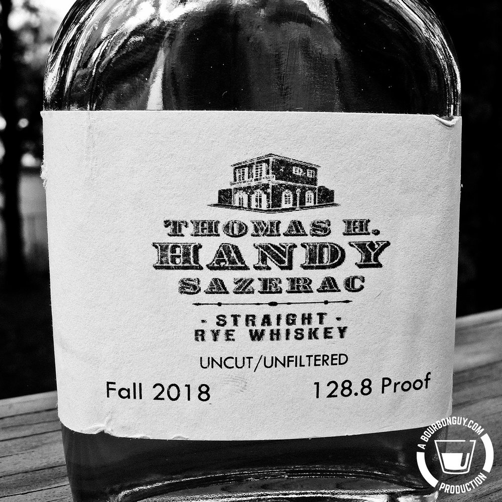 IMAGE: Close up of the label of the sample of Thomas H. Handy. The label is lightly torn. It has the Handy logo and the words: Uncut/Unfiltered, Fall 2018, and 128.8 Proof.