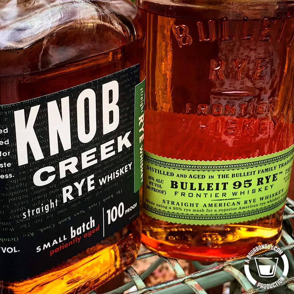 IMAGE: A closely cropped bottle of Knob Creek Rye and a bottle of Bulleit 95 Rye sitting on a wire table.