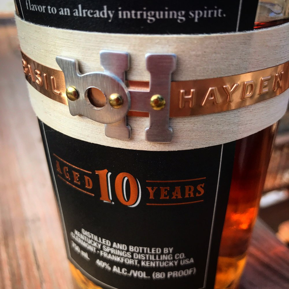 "IMAGE: The wood and metal band on a bottle of Basil Hayden's bourbon. Below that the words ""Aged 10 Years."""